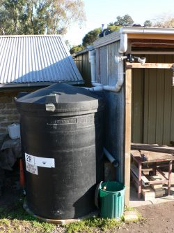 Small home water tank setup with water pipes feeding into small black tank