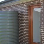 Side of brick house with slimline steel tank on very green grass