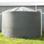 Small home poly water tank sitting on gree grass