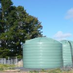 Two green poly tanks in a tree covered property