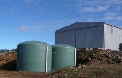 Two very large green water tanks being burried in the ground