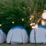 Tents in a line lit up by a long chain of lights