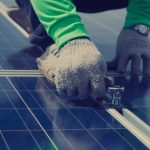 Close up of man installing solar panel with wrench