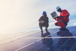 Two workers inspecting a large solar panel